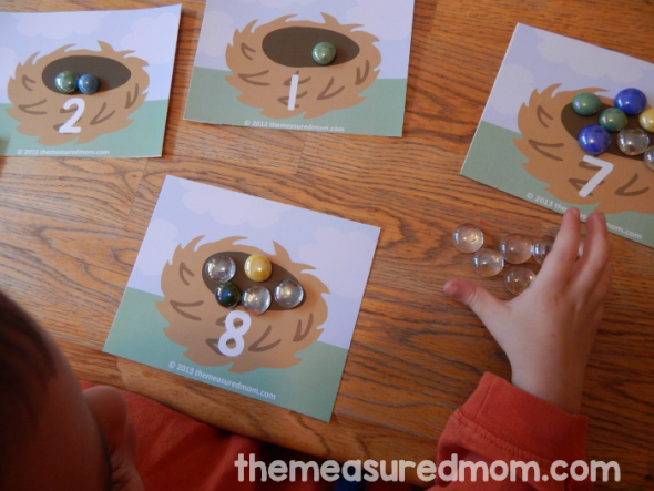 child placing gems on counting mat