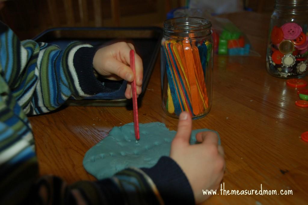 child sticking craft sticks into playdough