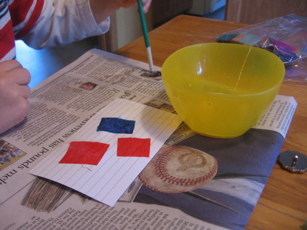 child painting glue on newspaper and index cards