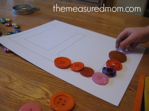 child placing buttons into block letter E
