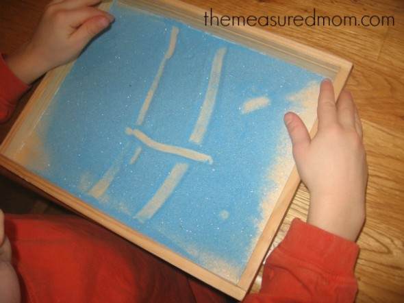 child making the letter H with colored sand