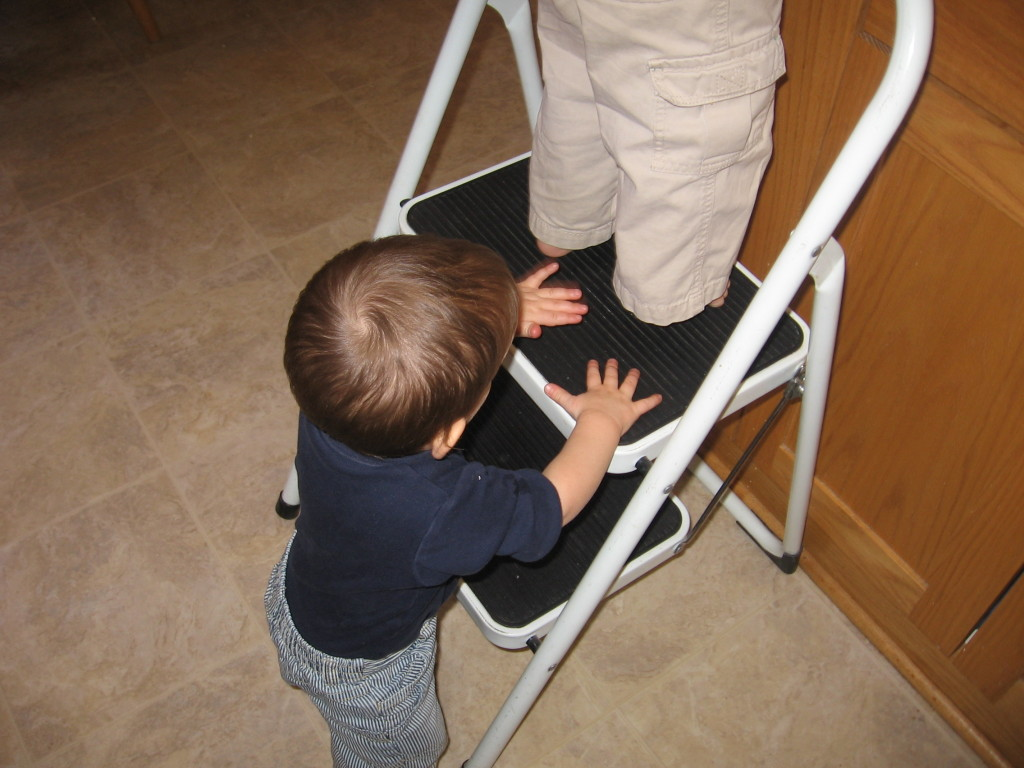 baby holding on to stool while child works
