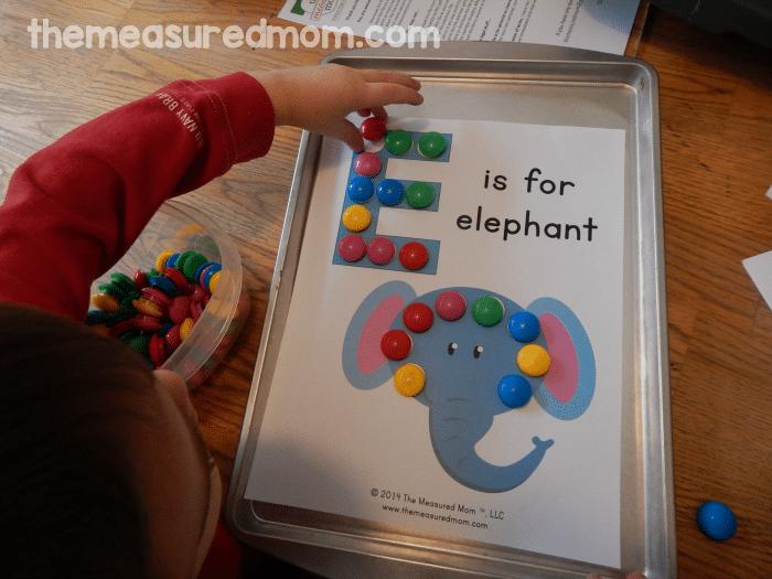 child placing magnets on worksheet