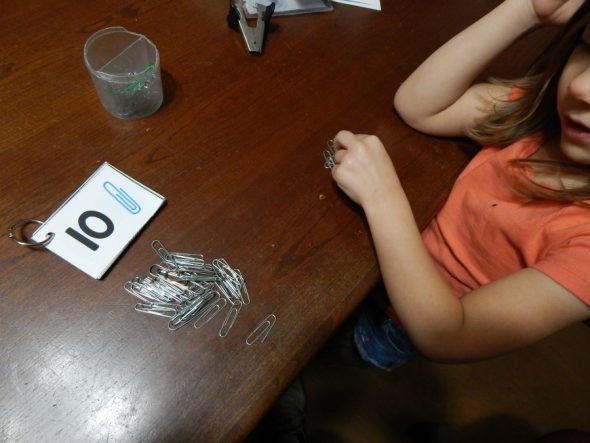child counting paper clips